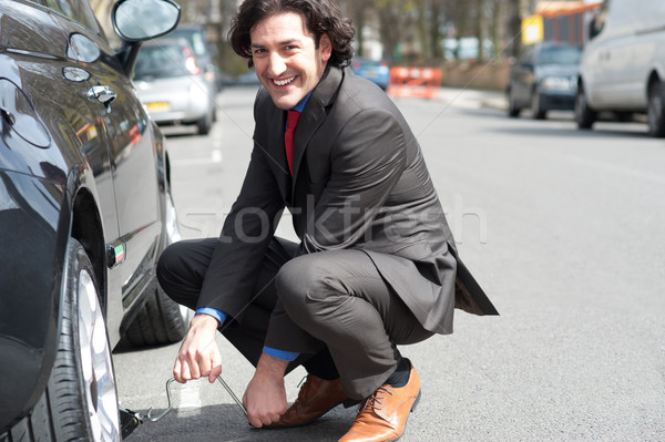 Businessman repairing car roadside Stock photo © stockyimages