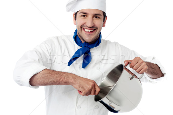 Smiling young chef holding vessel Stock photo © stockyimages