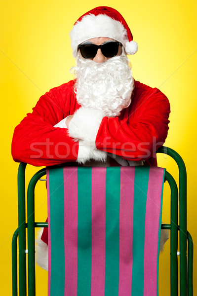 Stylish male santa posing with a deckchair Stock photo © stockyimages