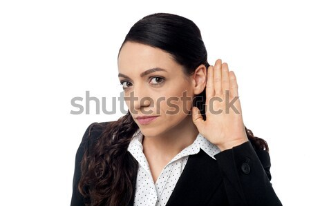 Business woman with hand to ear Stock photo © stockyimages