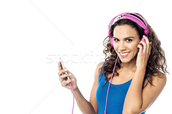 Enyém kedvenc dal fiatal nő hallgat mobiltelefon Stock fotó © stockyimages