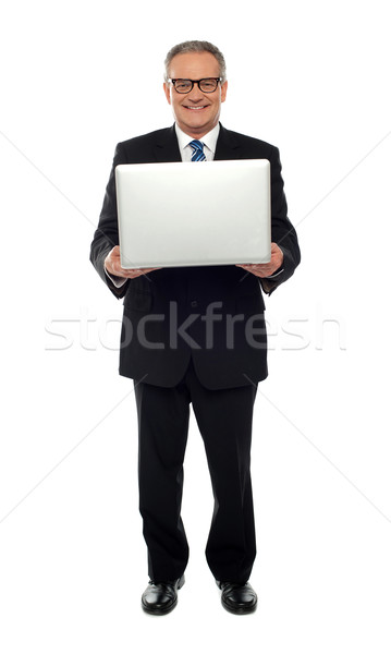 Experienced business person holding laptop Stock photo © stockyimages