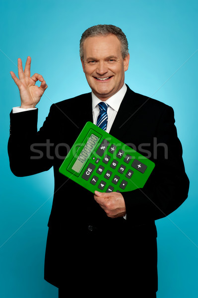 Confident executive holding calculator and gesturing okay sign Stock photo © stockyimages