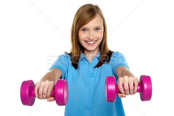 Adorable teen holding dumbbells in her outstretched arms Stock photo © stockyimages