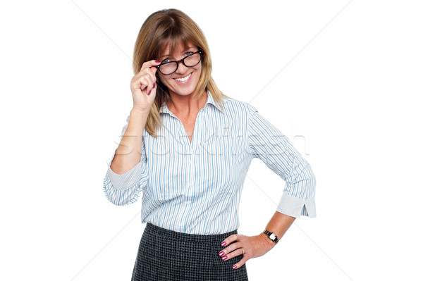 Cheerful corporate lady adjusting her spectacles Stock photo © stockyimages