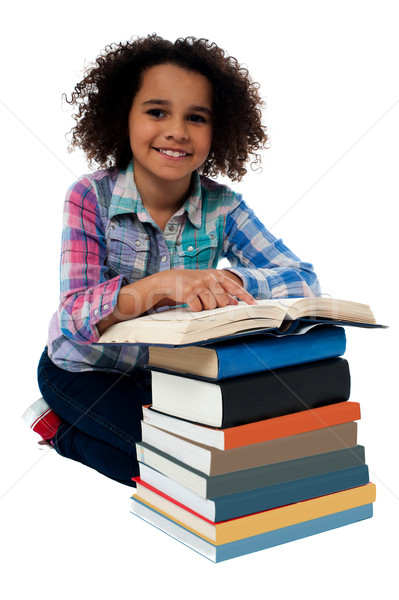 Happy schoolgirl reading a textbook Stock photo © stockyimages