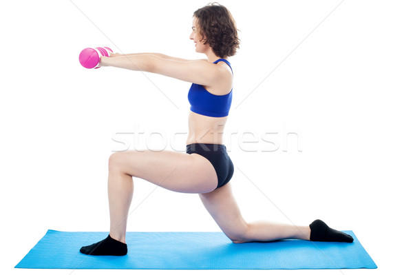 Woman exercising with dumbbells, arms outstretched Stock photo © stockyimages