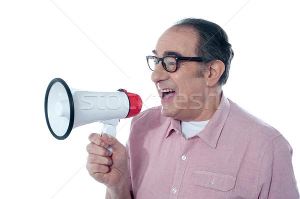 Elder casual man shouting through megaphone Stock photo © stockyimages
