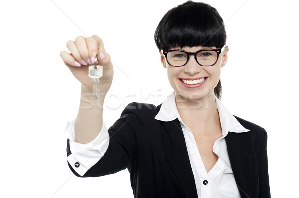 Smiling female executive handing over the key Stock photo © stockyimages