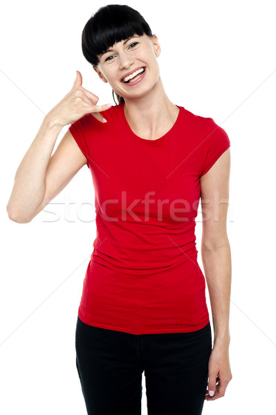 Cheerful brunette gesturing a mock call Stock photo © stockyimages