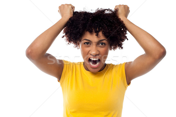 Angry young woman pulling her hair out Stock photo © stockyimages