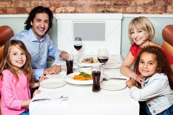 Cheerful family of four in a restaurant Stock photo © stockyimages