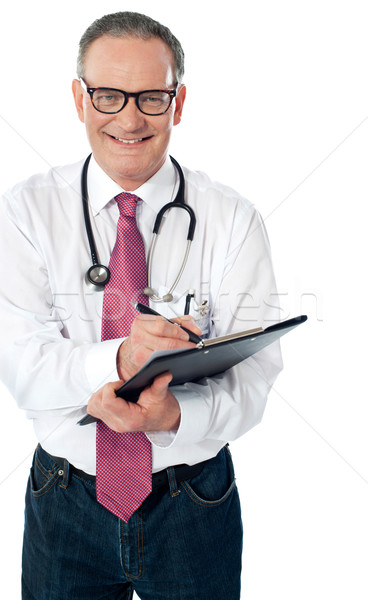 Happy smiling matured doctor writing on clipboard Stock photo © stockyimages