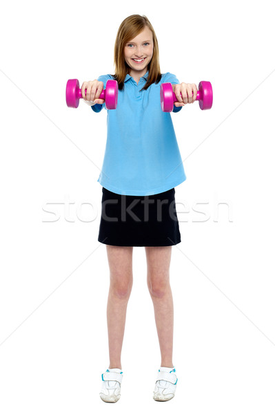 Slim girl striking a pose with dumbbells. Lifting weights Stock photo © stockyimages