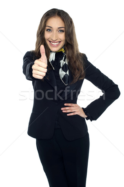Joyous young stewardess gesturing thumbs up Stock photo © stockyimages
