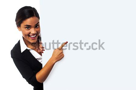 Experienced female executive pointing away Stock photo © stockyimages