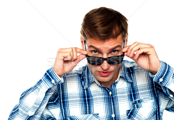 Confident young man peeping from goggles Stock photo © stockyimages