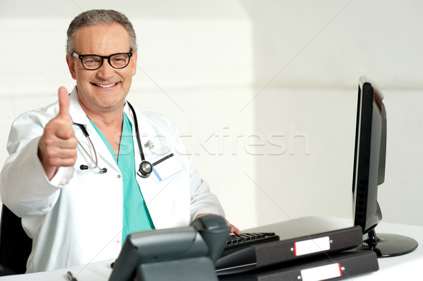 Smiling doctor gesturing thumbs up to camera Stock photo © stockyimages