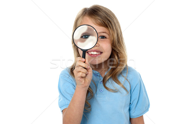 Smiling kid with magnifying glass Stock photo © stockyimages