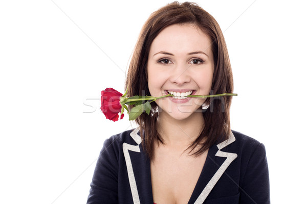 Young female holding rose between her teeth Stock photo © stockyimages