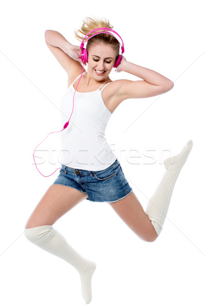 Music lover jumping high in the air Stock photo © stockyimages