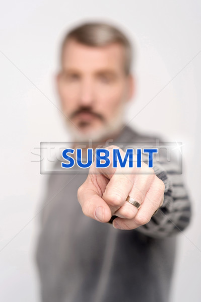 Man pressing virtual submit button Stock photo © stockyimages