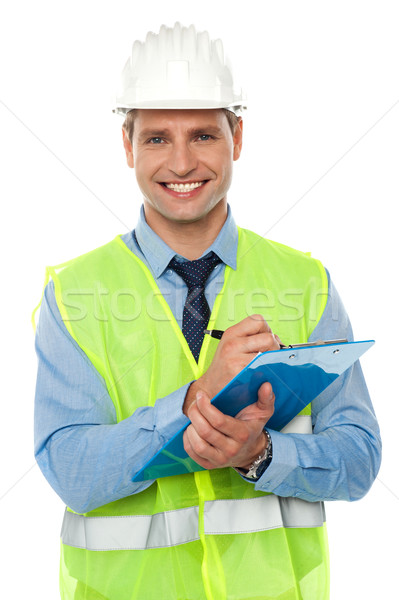 Construction engineer writing on notepad Stock photo © stockyimages
