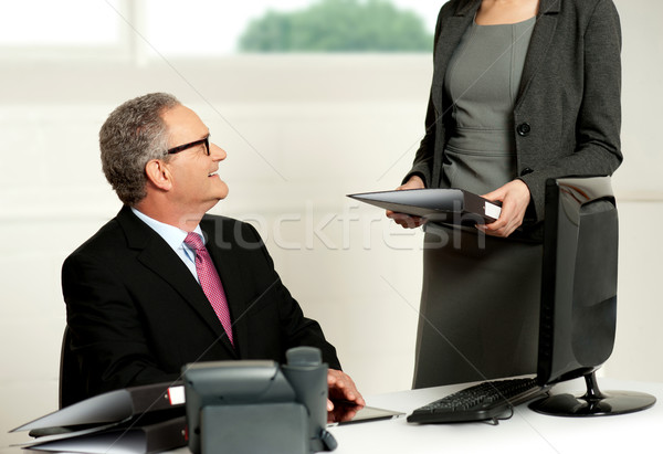 Smiling aged male boss looking at secretary Stock photo © stockyimages