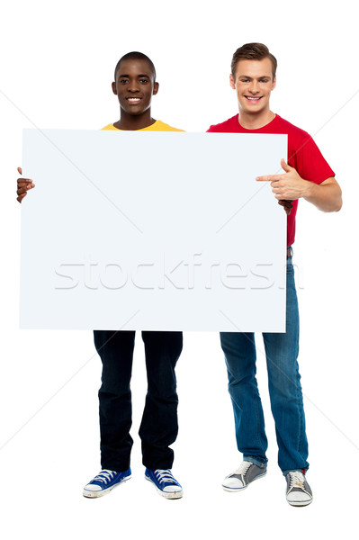 Smiling guys with white ad board Stock photo © stockyimages