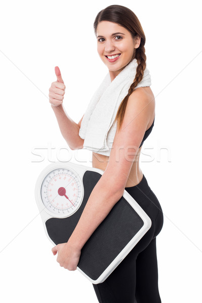 Happy Fitness woman with a weighing scale Stock photo © stockyimages