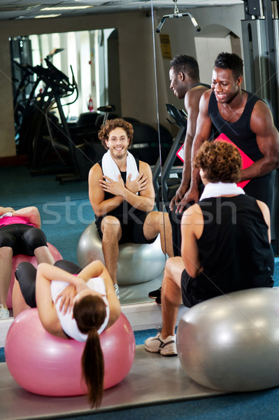 Trainer instructing gym clients on how to use exercise ball Stock photo © stockyimages