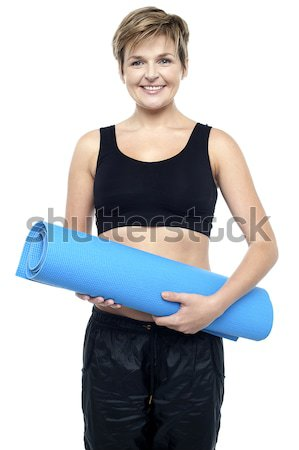 Health conscious woman holding blue exercise mat Stock photo © stockyimages