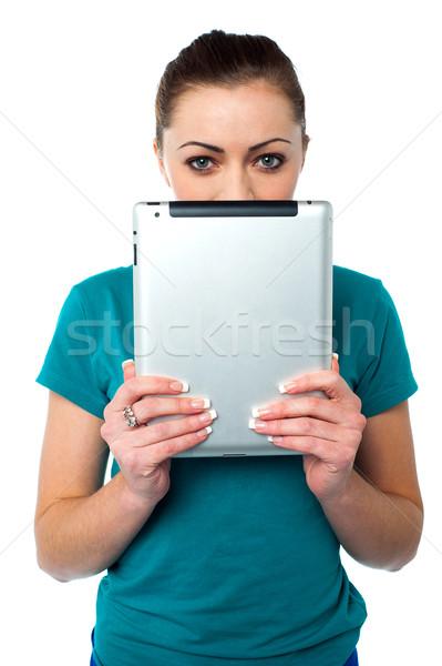 Félénk csinos modell rejtőzködik arc táblagép Stock fotó © stockyimages