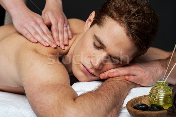 Young man getting spa massage Stock photo © stockyimages