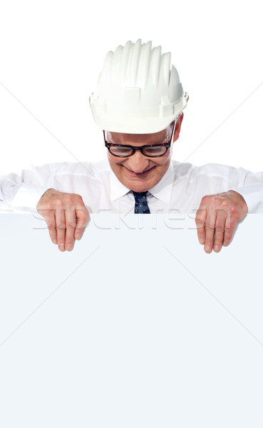 Aged builder wearning and holding a blank poster Stock photo © stockyimages