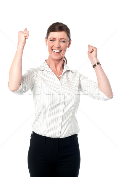 Excited corporate lady with clenched fists Stock photo © stockyimages