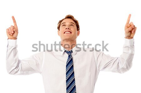 Male executive looking and pointing upwards Stock photo © stockyimages