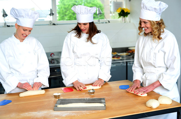 Beautiful female chefs kneading dough Stock photo © stockyimages