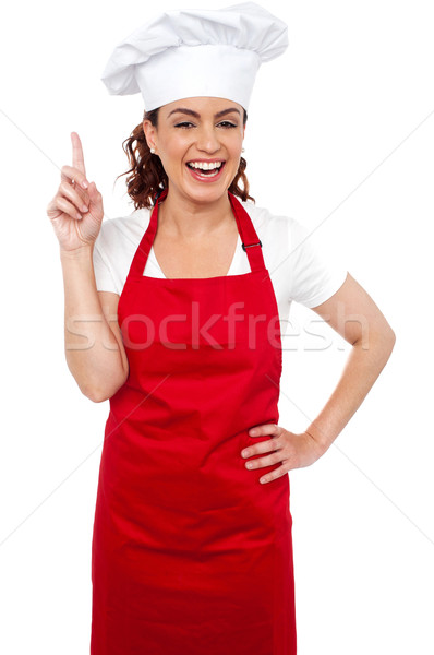 Beautiful smiling female chef indicating upwards Stock photo © stockyimages