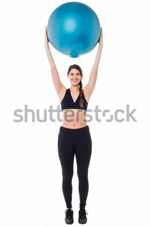 Fitness enthusiast holding ball above her head Stock photo © stockyimages