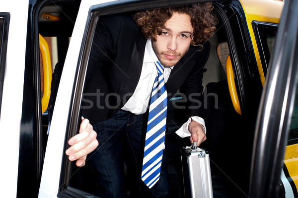 Corporate guy getting out of a taxi cab Stock photo © stockyimages