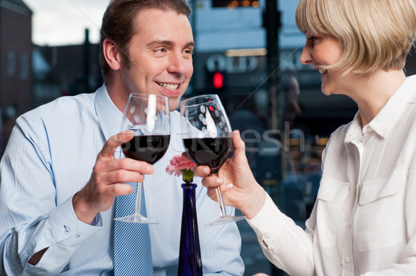 Happy couple raises a glass of red wine Stock photo © stockyimages