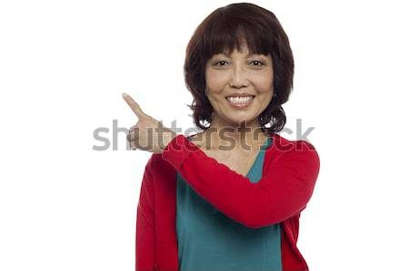 Beautiful woman indication copy space area Stock photo © stockyimages