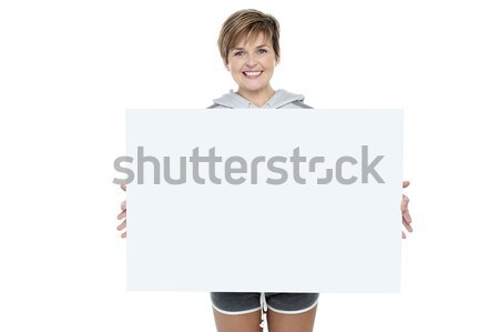 Charming young woman holding white ad board Stock photo © stockyimages