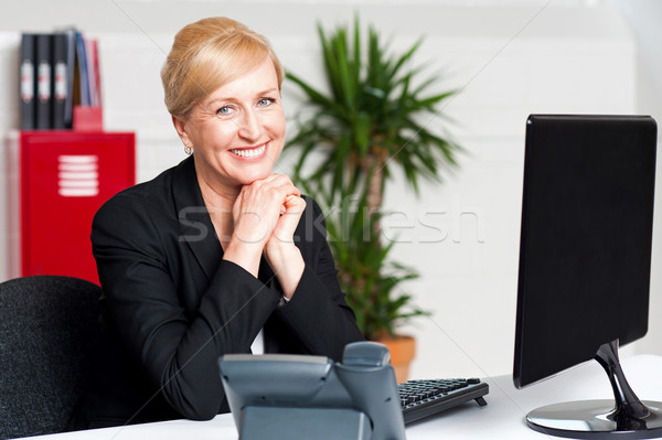 Aged businesswoman sitting with hands on chin Stock photo © stockyimages