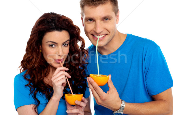Closeup of couple cuddling and sipping orange juice Stock photo © stockyimages