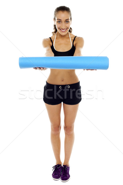 Woman holding a blue mat in her outstretched arms Stock photo © stockyimages
