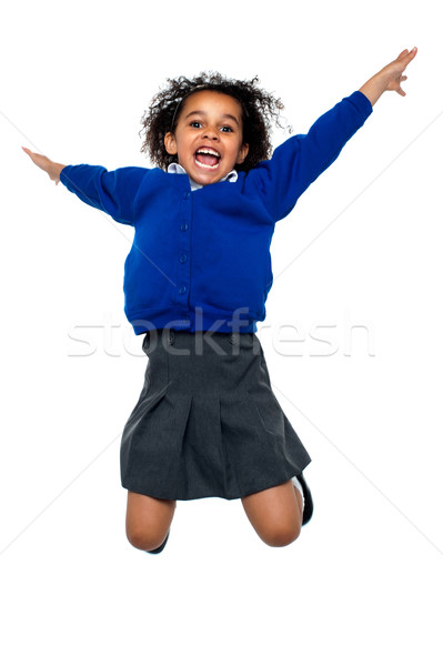 Jubilant school kid jumping high up in the air Stock photo © stockyimages