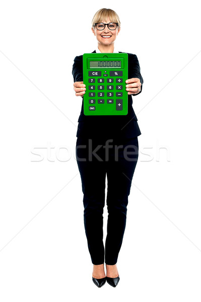 Woman in business suit displaying large green calculator Stock photo © stockyimages