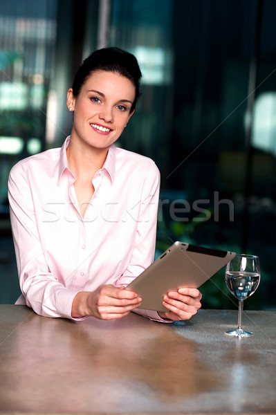 Businesswoman browsing on tablet pc with a drink beside Stock photo © stockyimages